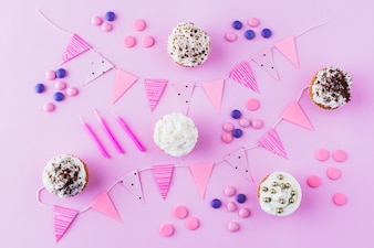 Cupcakes; candies; candles and bunting on pink backdrop