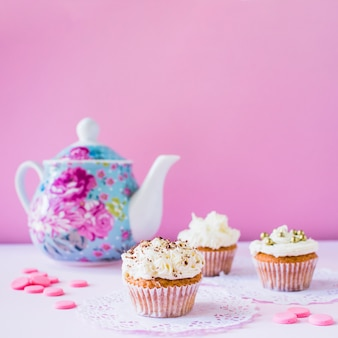 Cupcakes; candies and teapot on white surface