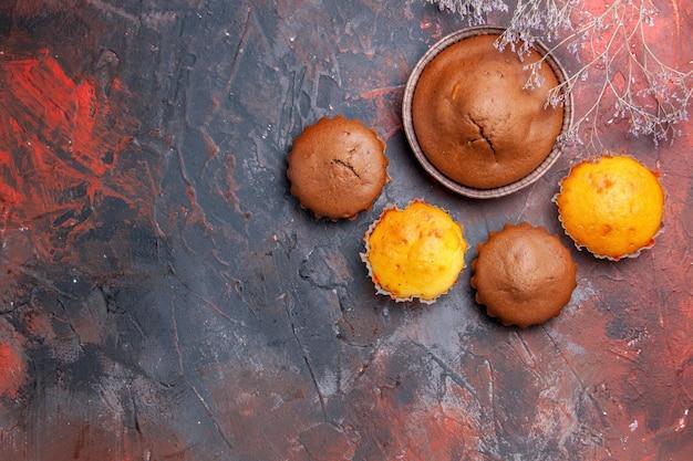 青赤のテーブルにカップケーキチョコレートケーキと4つの異なるカップケーキ