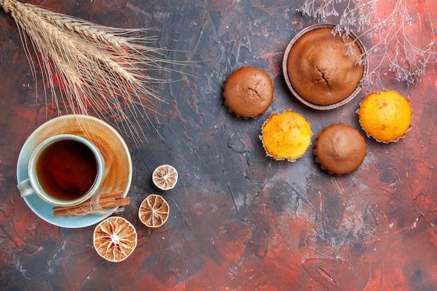 Cupcakes una tazza tealemon torta al cioccolato quattro cupcakes sul tavolo blu-rosso