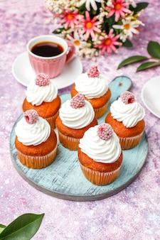Кексы украшали взбитыми сливками и замороженной малиной.