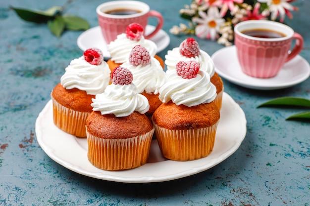 컵케익은 휘핑 크림과 냉동 산딸기를 장식했습니다.
