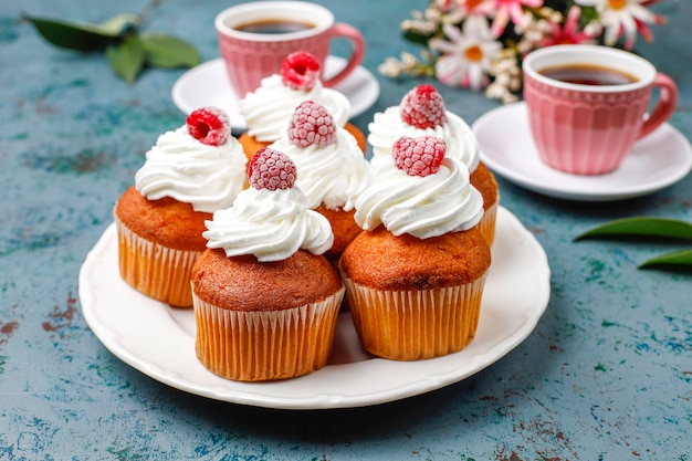Cupcakes decorated whipped cream and frozen raspberries. Free Photo