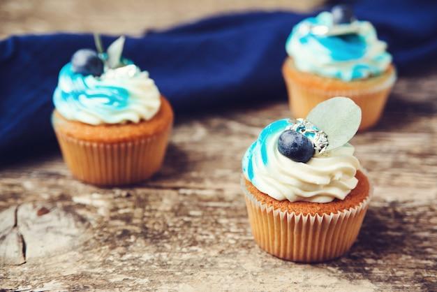 Кексы украшены синим кремом и свежими ягодами. вкусные кексы с черникой на деревянных фоне. день рождения кексы для празднования.
