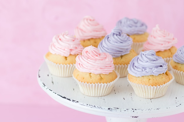 Cupcakes decorated with pink and violet buttercream on shabby shic stand