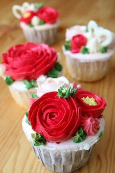 Cupcakes decorated with red flower shaped whipped cream on wooden table with selective focus