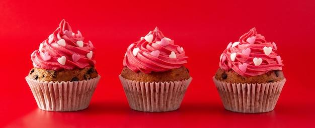 赤い背景のパノラマビューでバレンタインデーの砂糖の心で飾られたカップケーキ