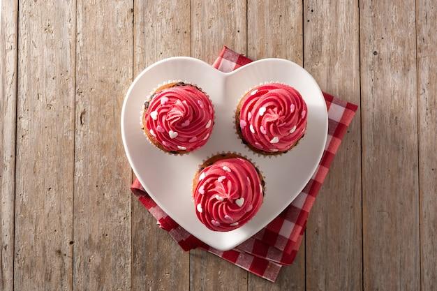 Кексы, украшенные сахарными сердечками на день святого валентина на деревянном столе. вид сверху