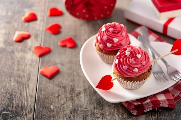 나무 테이블에 발렌타인 설탕 하트 장식 컵 케이크