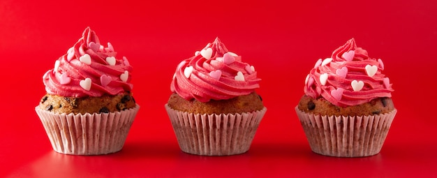 Cupcakes decorated with sugar hearts for valentine's day on red background panorama view