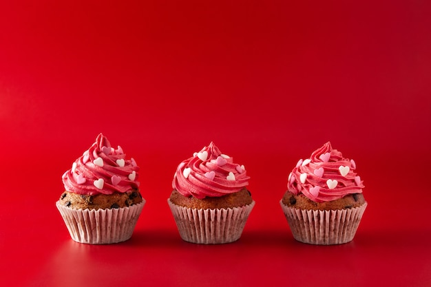 Cupcakes decorated with sugar hearts for valentine's day on red background