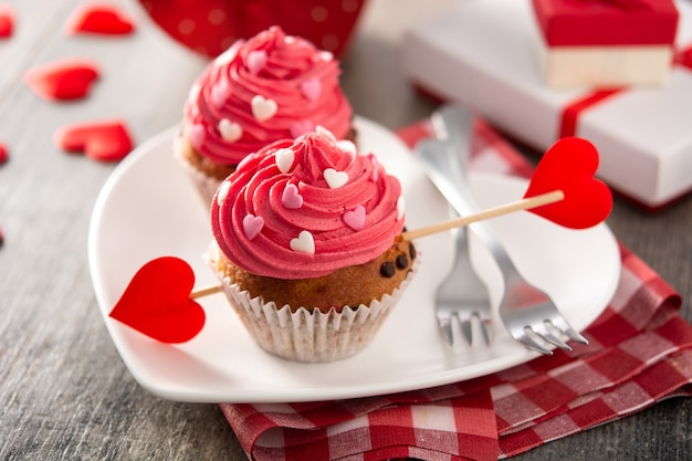 Cupcakes decorated with sugar hearts for valentine's day on wooden table