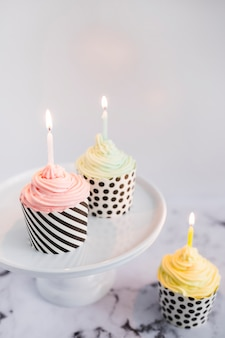 Cupcakes on display with light candles