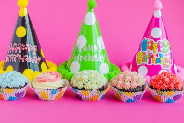 Cupcakes e cappelli di partito su rosa