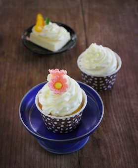 Cupcakes served in polka dot paper mould with buttercream frosting put on wood background