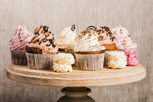 Cupcakes and whipped creams on wooden stand