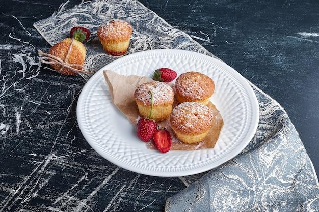 Cupcakes in un piatto bianco con frutti di bosco.