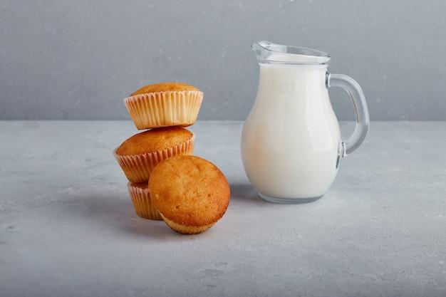 灰色の背景に牛乳の瓶とカップケーキ。