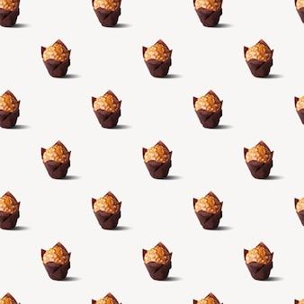 アーモンドと白い背景のシームレスなパターンの影とカップケーキ