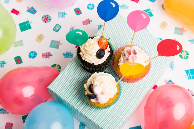 Cupcakes with balloon toppers on box