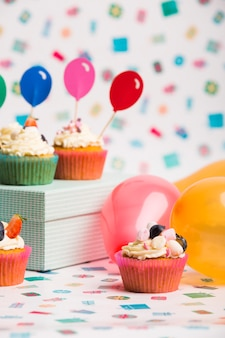 Cupcakes with balloons on table