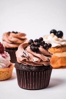 회색 벽에 고립 된 조명 아래 딸기와 초콜릿 컵 케이크