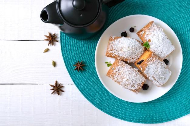 딸기와 흰색 나무 테이블에 접시에 설탕을 입힌 컵 케이크. 직사각형 머핀과 차. 평면도.