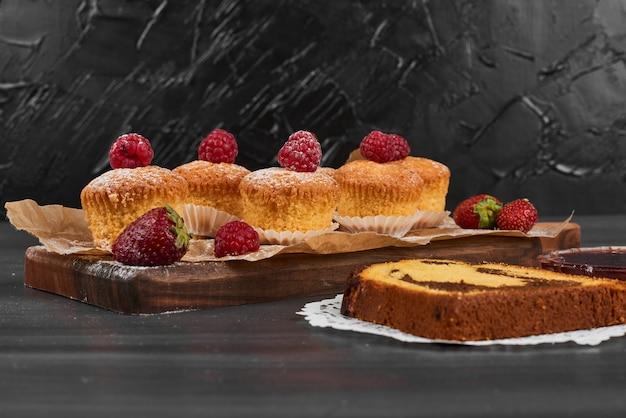 나무 보드에 딸기와 컵 케이크입니다.