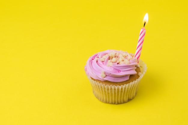 黄色い表面にベリークリームとキャンドルのカップケーキ
