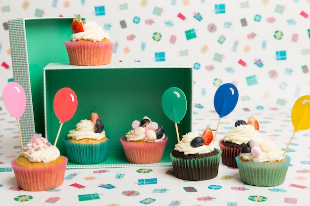 Cupcakes with bright balloon toppings on table