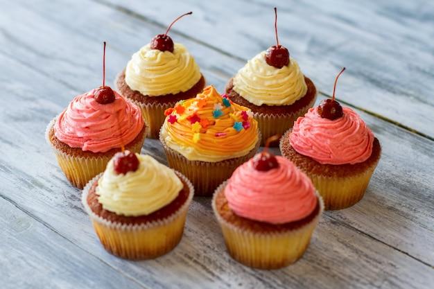 나무 표면에 밝은 설탕 장식 디저트가 있는 컵 케이크 일부 과자 구운 반죽과 버트는 어떻습니까?