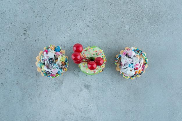 大理石の背景にキャンディーフィリングと小さなドーナツが入ったカップケーキ。高品質の写真