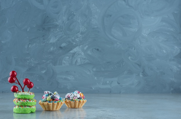 Cupcakes with candy fillings and small donuts on marble background. high quality photo