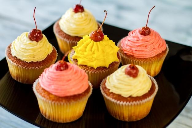 黒いプレートの上のペストリーの上にさくらんぼが入ったカップケーキは、さまざまなフレーバーの甘いお菓子を驚かせます...