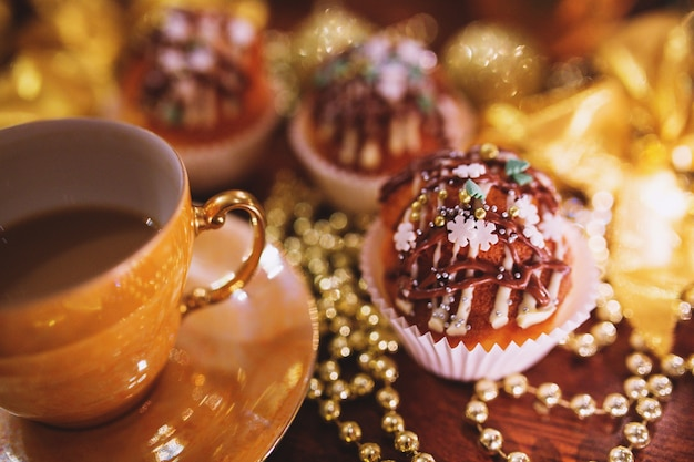 Cupcakes with christmas decoration and a cup
