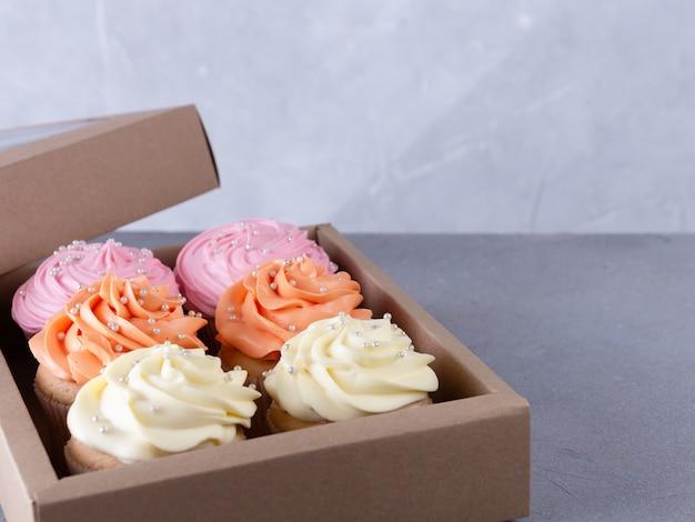 ギフトボックスにカラークリームのカップケーキ。