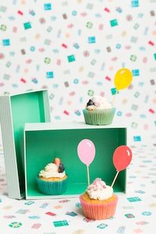 テーブルの上のカラフルな風船トッパーのカップケーキ
