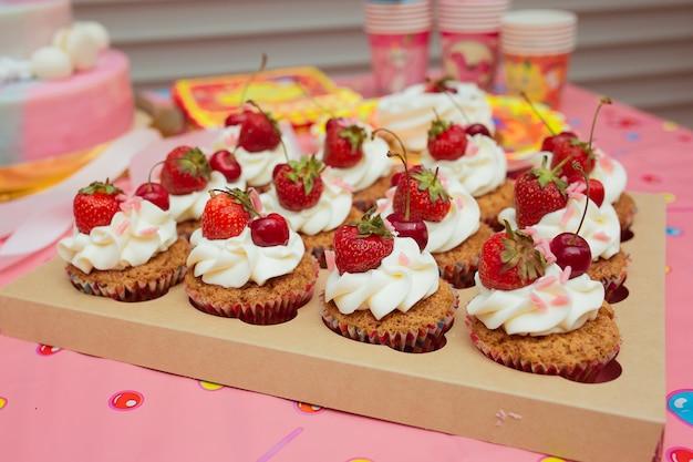 어린이 휴가에 크림과 딸기를 넣은 컵케이크