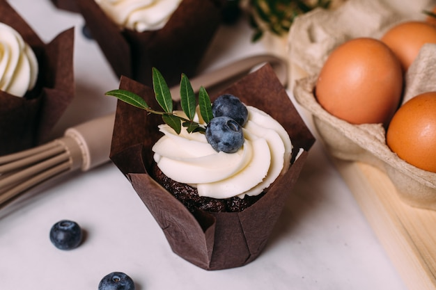 Cupcakes with cream and blueberries on kitchen table
