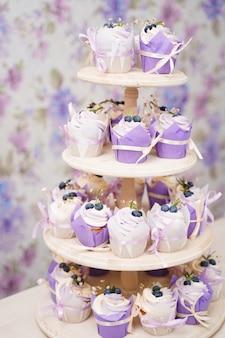 ブルーベリー、ローズマリー、花で飾られ、リボンで結ばれた紙のチューリップの形のクリームとカップケーキ。ラベンダークリームとバニラカップケーキ。テーママフィン。