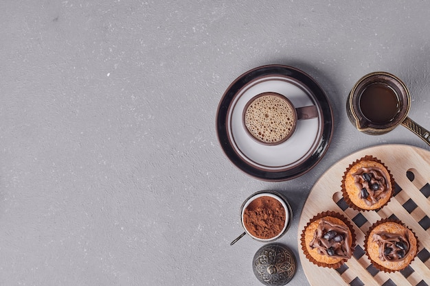 Cupcakes with a cup of coffee around.