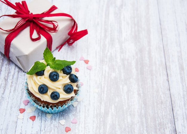 Cupcakes with fresh berries and gift box