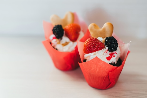 Cupcakes with fresh strawberries and blackberry berries and cream and sweet biscuits