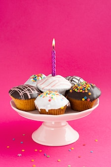 Cupcakes with glaze on colored background