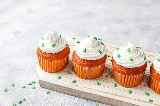 Cupcakes with green decorations on wood table