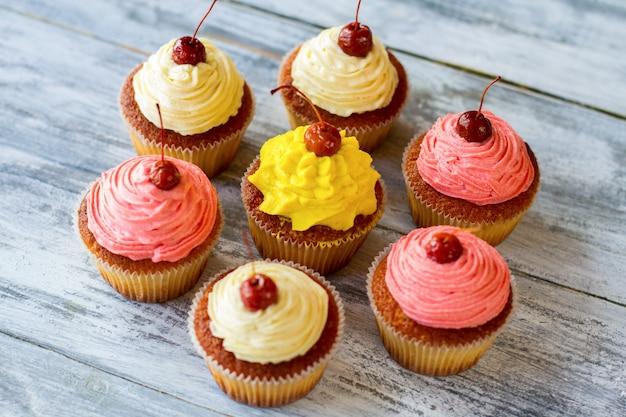 회색 배경에 디저트를 입힌 컵케이크는 집에서 신선한 재료와 간단한 음식으로 만든 달콤한 간식을 제공합니다.