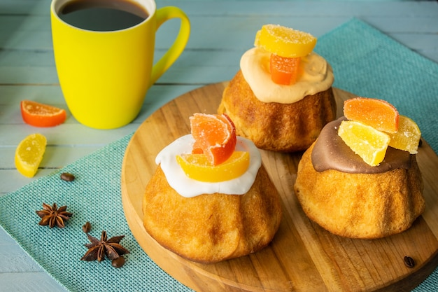 Cupcakes with icing imarmelade cup of coffee on a wooden background