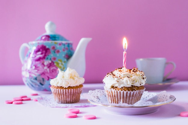 Cupcakes with illuminated candle on table top