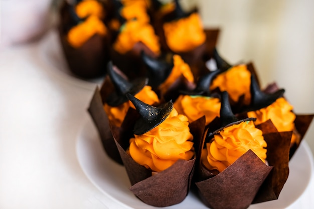 Cupcakes with orange cream and sweet black hats on the candy bar for the celebration of halloween