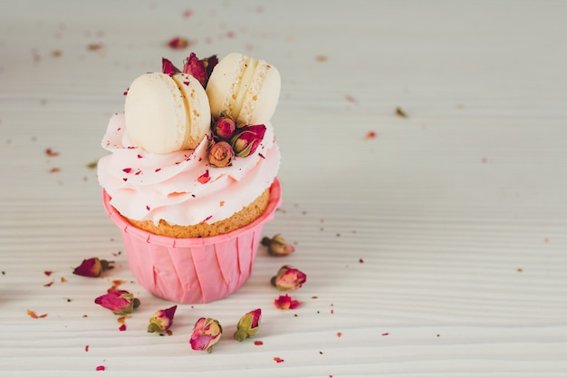 Cupcakes with pink cream, macaroons and roses